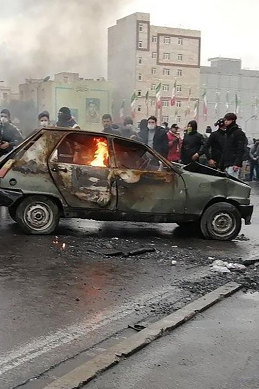 Iranian protesters gather around a burning car during a demonstration against an increase in gasoline prices in the capital Tehran