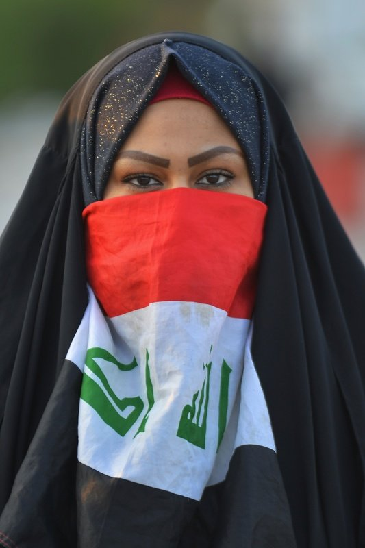 An Iraqi protester covers part of her face with the national flag during an anti-government demonstration in the central holy shrine city of Najaf