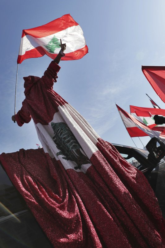 An anti-government protester wears a robe presenting the Lebanese national flag during an alternative independence celebrations at the Martyr square, in downtown Beirut