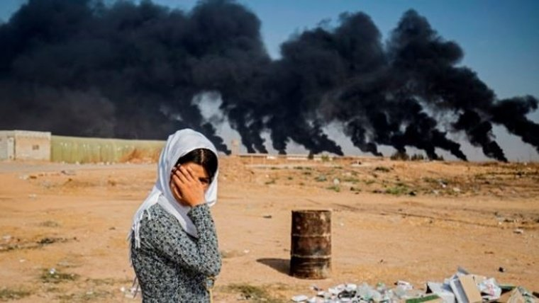 A woman covers her face as she stands on the outskirts of a town near the Syria-Turkey border, while smoke plumes meant to decrease visibility for Turkish warplanes billow from tire fires during a cross-border offensive, on October 16, 2019. Delil Souleiman/AFP/Getty Images