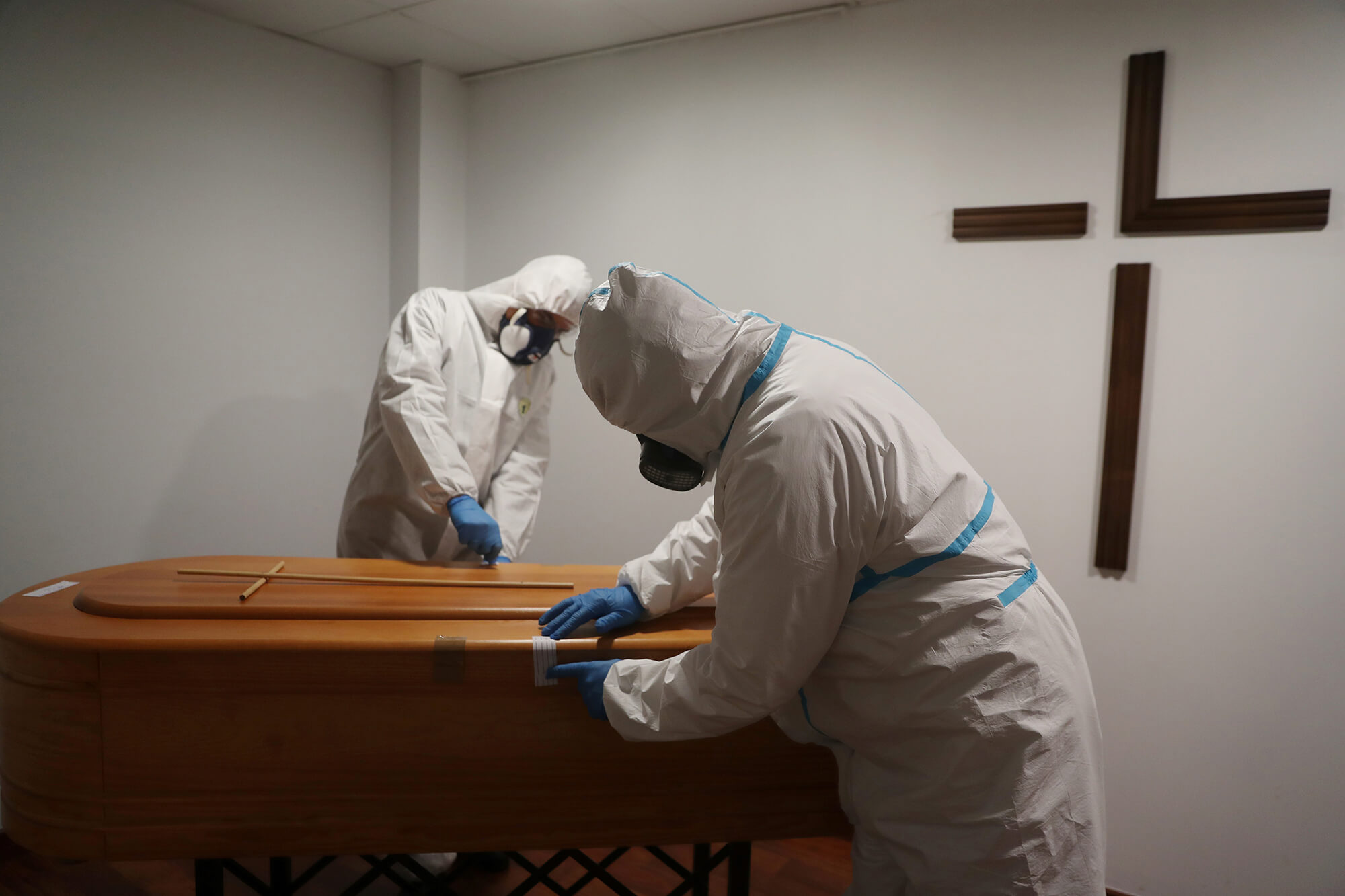Mortuary workers wearing protective gear are seen at the San Juan de la Cruz funeral home, amid the coronavirus disease outbreak.