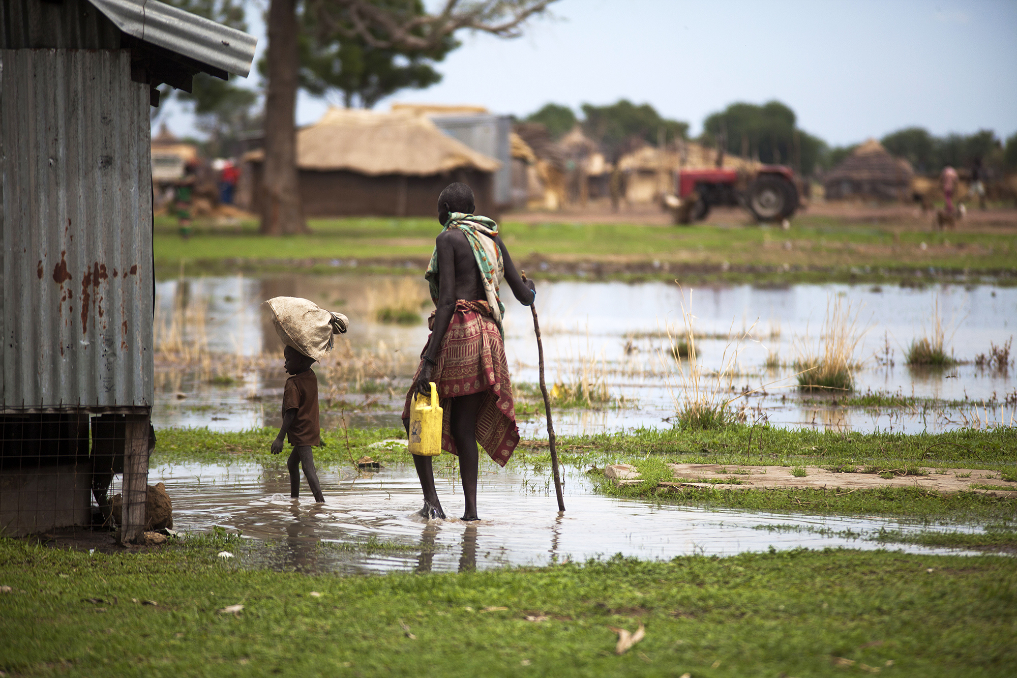 A woman with a boy walk in a flooded area in South Sudan