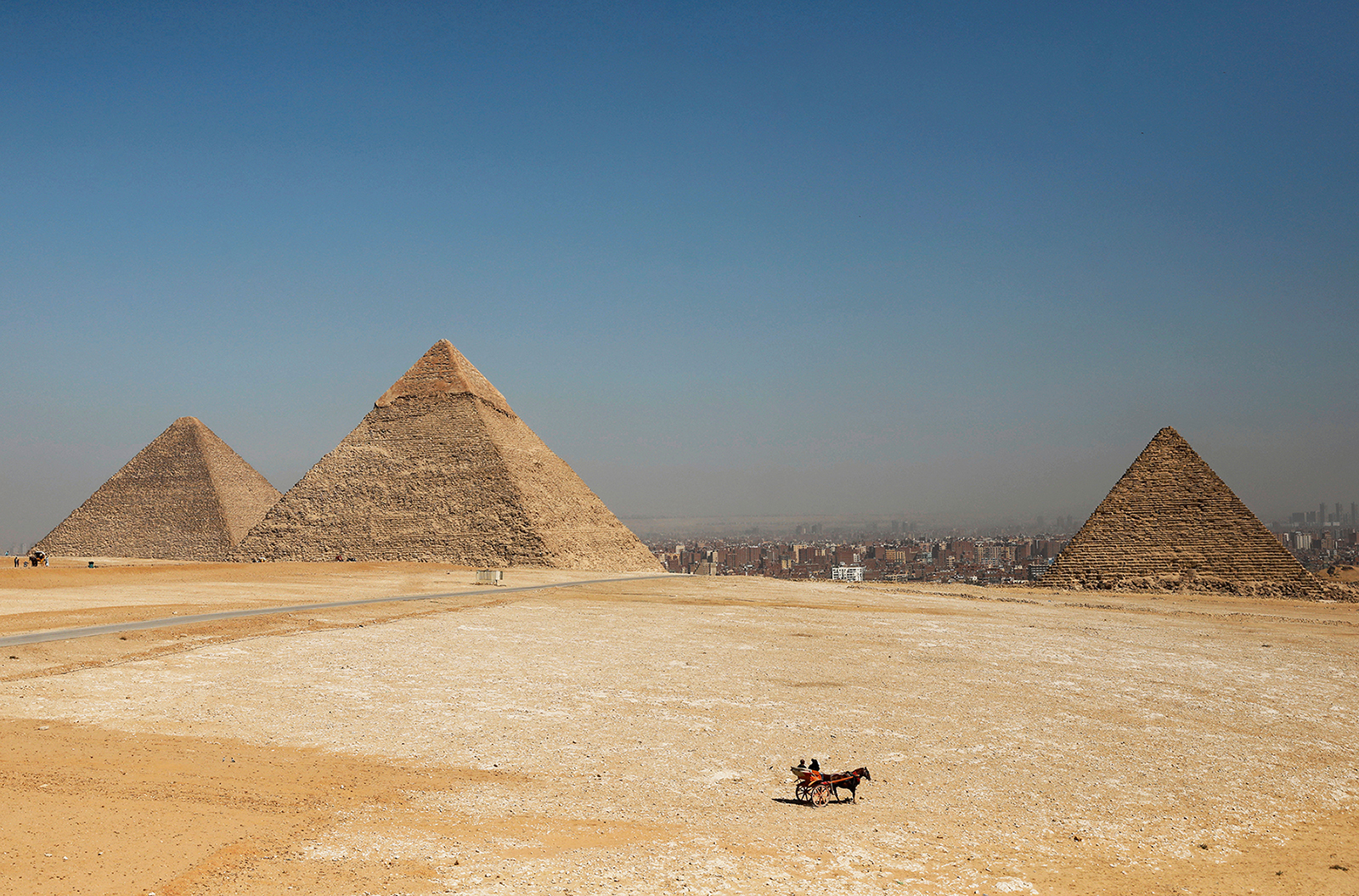 Tourists ride a horse-drawn cart in front of the Great Pyramids of Giza, on the outskirts of Cairo