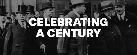 """Celebrating a Century"" in all capitalized white text on a black and white photo of formally dressed men in hats"