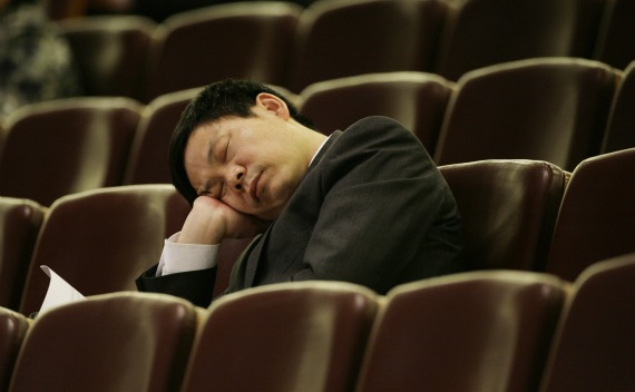 An unidentified official sleeps as Chinese Parliament chief Wu Bangguo delivers the work report of the National People's Congress Standing Committee during the second plenary session at the Great Hall of the People in Beijing on March 9, 2009.