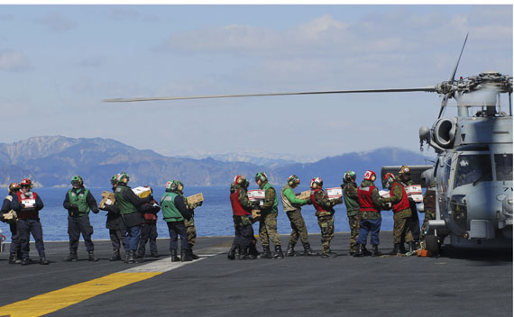 Sailors load food and humanitarian supplies onto a helicopter aboard the USS Ronald Reagan which is off the coast of Japan providing humanitarian assistance as directed in support of Operation Tomodachi, March 18, 2011.