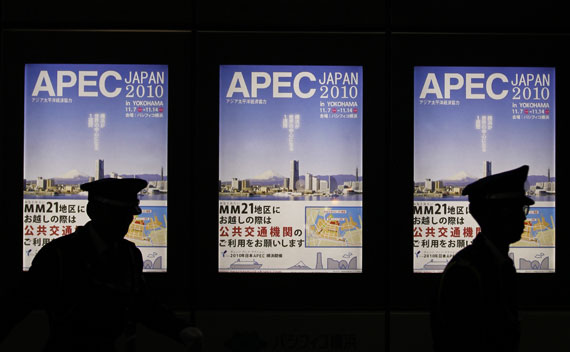 Policemen are silhouetted on signboards of APEC forum summit in Yokohama, south of Tokyo