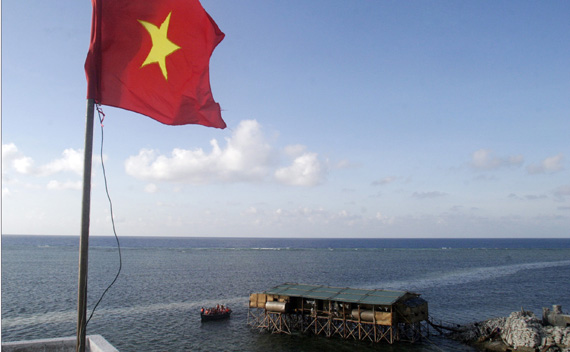 A Vietnamese flag flutters as a motorboat transporting Vietnamese navy personnel passes a construction site of a new pier on Truong Sa islands or Spratly islands
