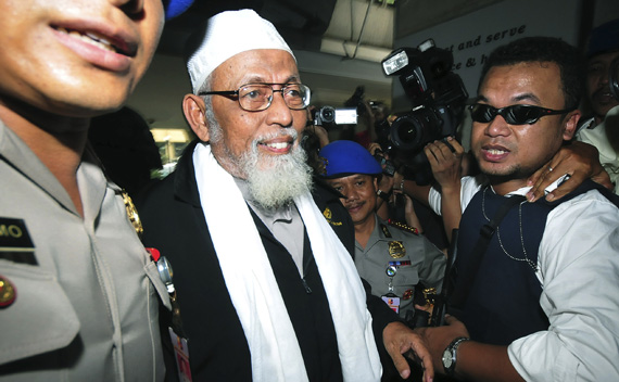 Indonesian Muslim cleric Abu Bakar Bashir is escorted by the police as he arrives at the police headquarters in Jakarta