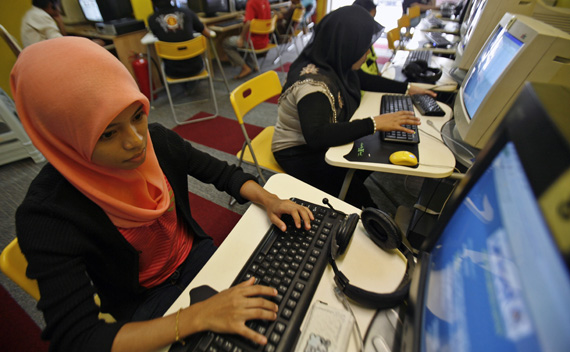 Mas Ayu Adnan, a student, checks her assignment at a cybercafe in Kuala Lumpur August 11, 2009.