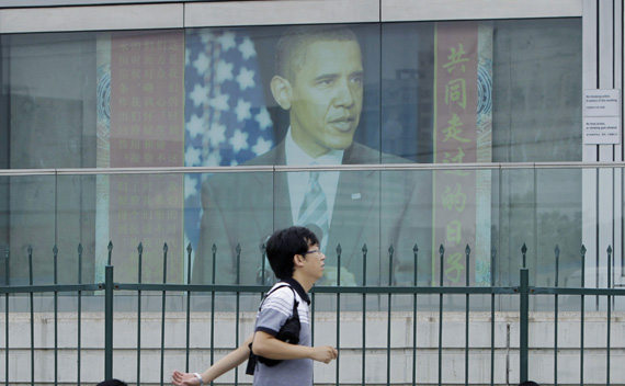 A man walks past a picture of U.S. President Obama outside the U.S. embassy in Beijing