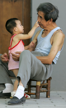 A 76-year-old man plays with his granddaughter at a hutong (traditional neighbourhood) in Beijing August 21, 2006. China's one-child policy has led to an aging population and labour shortages that could undermine a key basis for the country's economic growth -- its seemingly endless supply of cheap workers, a newspaper said on Monday. Photo courtesy REUTERS/Jason Lee