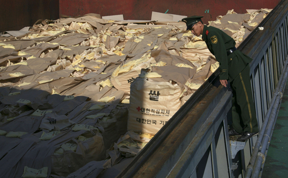 A Chinese frontier policeman checks sacks of rice from South Korea, which will be sent to North Korea, at Dandong port, Liaoning province October 29, 2010.