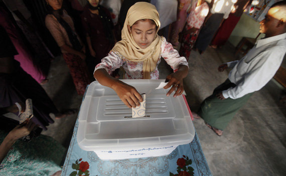 A woman casts her ballot at the polling station in Sittwe