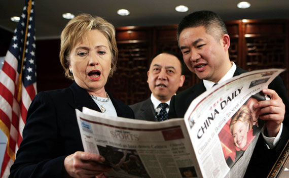 U.S. Secretary of State Hillary Clinton (L) reacts while reading a local English newspaper before conducting a Web chat with Chinese internet users at the U.S. embassy in Beijing February 22, 2009. REUTERS/China Daily