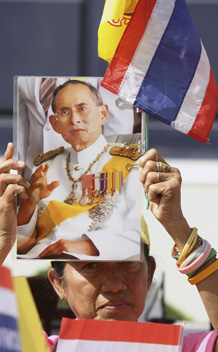 A woman holds a portrait of Thailand's King Bhumibol Adulyadej on his 83rd birthday in Bangkok