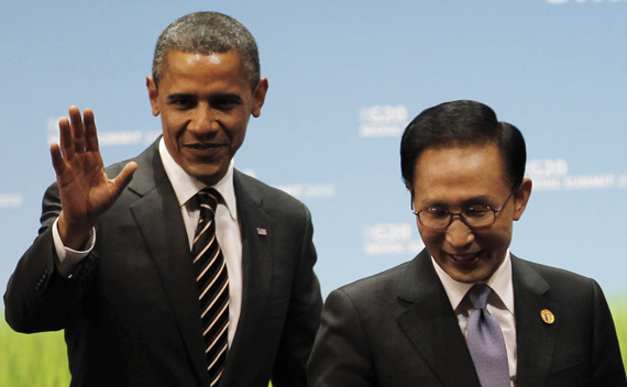 U.S. President Obama gestures next to South Korean President Lee on stage at the end of the G20 Summit in Seoul
