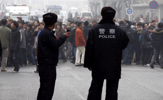 Policemen watch a crowd that gathered outside a McDonald's restaurant after internet social networks called for a