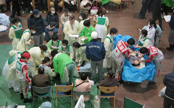 Survivors of an 8.9-magnitude earthquake and tsunami receive treatment at the Ishinomaki Red Cross hospital in Miyagi prefecture March 12, 2011.