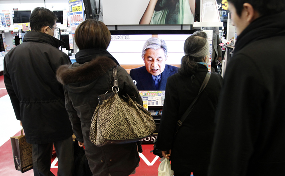 People watch a television broadcasting Japan's Emperor Akihito's televised address to the nation at an electronics retail store in Tokyo.