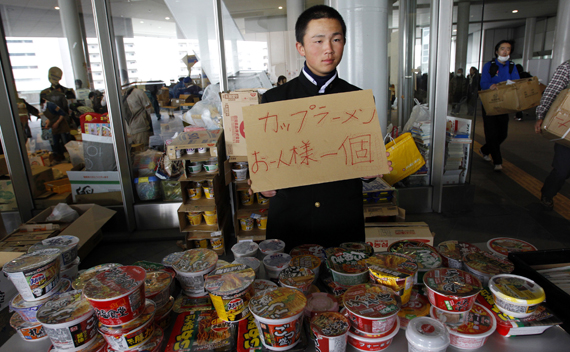 A student volunteer holds a sign in front of instant noodles for evacuees from Futaba, a city near the quake-stricken Fukushima Daiichi nuclear power plant, at the evacuees' new shelter Saitama Super Arena, near Tokyo March 20, 2011, nine days after an earthquake and tsunami hit Japan.