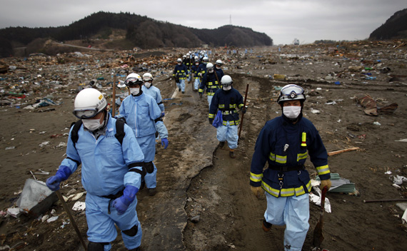 Rescue workers make their way through an area devastated by a tsunami as they search for victims in Rikuzentakata March 21, 2011.