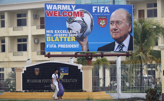 A couple walks below a welcome board for FIFA President Sepp Blatter outside the Myanmar Football Federation in Yangon March 14, 2011.