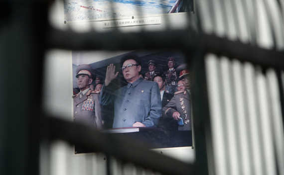 A billboard depicting North Korean leader Kim Jong-il is seen through the fence of the North Korea embassy in Beijing January 21, 2011.