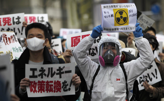 Protesters take part in an anti-nuclear rally in Tokyo March 27, 2011. The sign on the left reads,