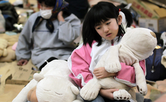 A girl holds her soft toy at an evacuation center in Koriyama, Fukushima Prefecture, northern Japan, March 31, 2011