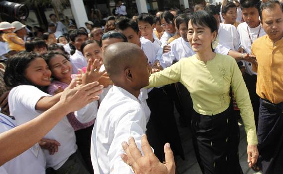 Myanmar's pro-democracy leader Aung San Suu Kyi shakes hand with people in Yangon