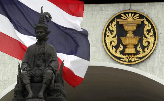 A Thai national flag flutters in the wind behind a statue of King Rama VII in front of the parliament building in Bangkok, May 10, 2011, ahead of a July 3 election.