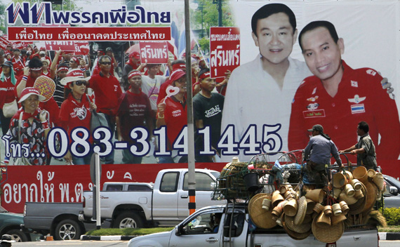 Men atop a truck travel past an election campaign poster showing a candidate for the opposition Puea Thai party posing with ousted former Prime Minister Thaksin Shinawatra in Thailand's Surin province April 26, 2011.