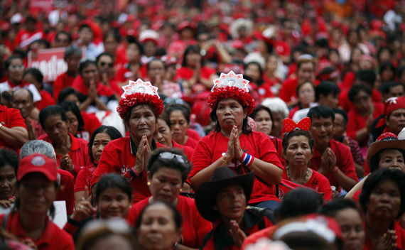 Anti-government ''red shirt'' protesters wear hats with pictures of toppled premier Thaksin Shinawatra as they pray during a rally at Ratchaprasong intersection at Bangkok's shopping district May 19, 2011. Thousands of