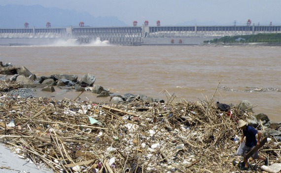 A worker clears floating garbage on the Yangtze River near the Three Gorges Dam in Yichang, Hubei province on August 1, 2010.