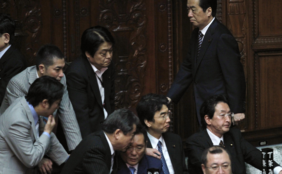 Japan's Prime Minister Naoto Kan (R) walks past lawmakers to cast a vote against the opposition-sponsored no-confidence motion in parliament in Tokyo June 2, 2011. Kan survived a no-confidence vote in parliament on Thursday, but the unpopular leader will still struggle to break a policy deadlock given a split in his own party and a divided parliament.