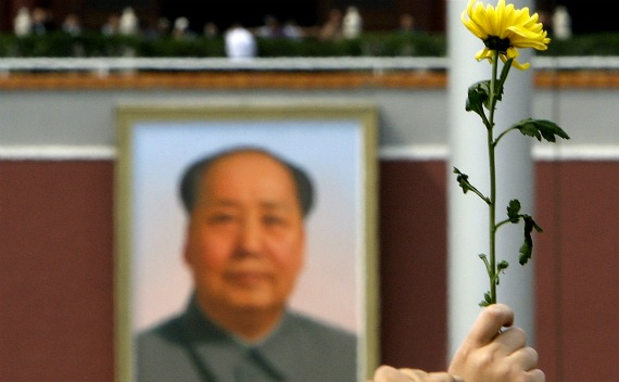 A woman holds a flower aloft in front of the portrait of Chairman Mao Zedong in Beijing's Tiananmen Square on May 19, 2008.