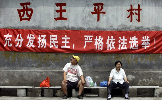 "Villagers rest under a campaign banner in the run-up to a democratic election for village committee at Xiwangping Village, in Beijing's Mentougou District on June 18,2010. The banner reads: ""fully develop democracy, strictly elect in accordance to law"""