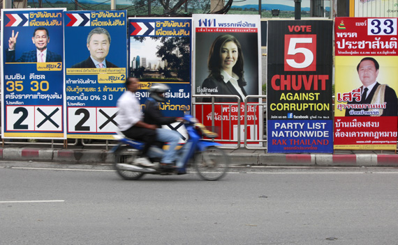 A motorcyclist rides past posters of candidates for the upcoming mayoral elections in Bangkok June 13, 2011.