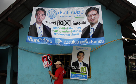 A supporter of Yingluck Shinawatra, sister of toppled premier Thaksin Shinawatra and the prime ministerial candidate for the country's biggest opposition Pheu Thai Party, holds her poster in front of a building decorated with banners of the Democrat party in Bangkok's notorious Klong Toey slum June 21, 2011.