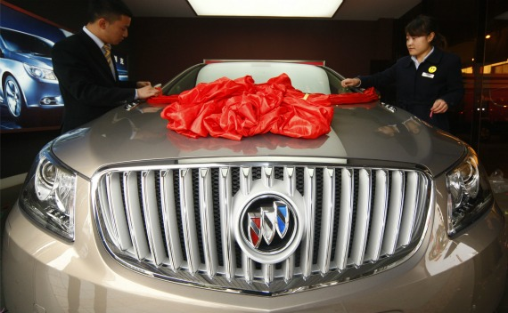 Employees decorate a Buick Regal car at a General Motors auto dealership in Suining, Sichuan province on November 18, 2010.