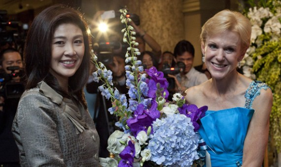Thailand's Prime Minister-elect Yingluck Shinawatra (L) poses for photographers as she gives United States ambassador to Thailand Kristie Kenney a bouquet of flowers ahead of U.S. Independence Day celebrations in Bangkok July 5, 2011.