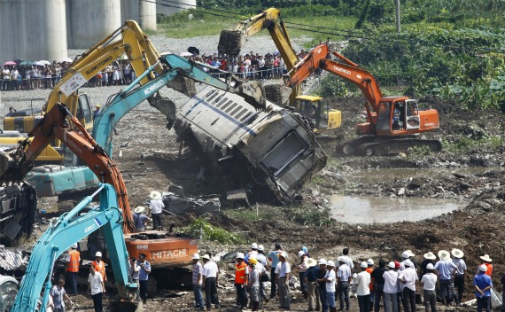 Workers and rescuers look on as excavators dig through the wreckage after a high speed train crashed into a stalled train in Wenzhou, Zhejiang province on July 24, 2011.