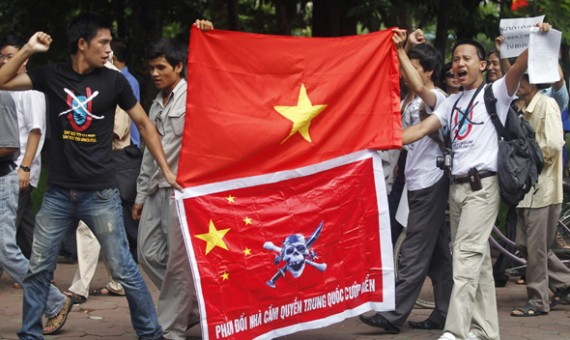 Anti-China protesters hold a Vietnamese flag (top) and a Chinese flag with an image of the pirate skull and crossbones (bottom) during a demonstration around Hoan Kiem lake in Hanoi July 24, 2011.