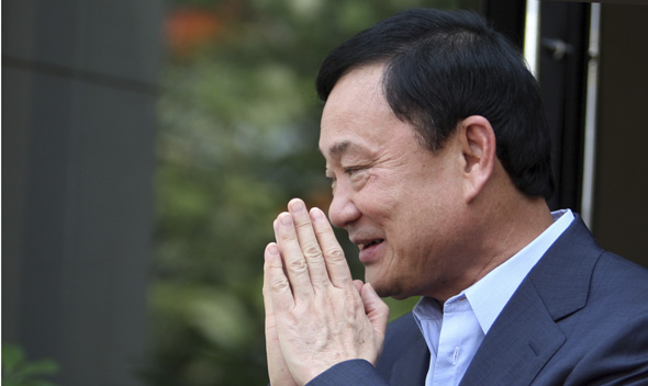 Thailand's former premier Thaksin Shinawatra greets journalists outside his home in Dubai.