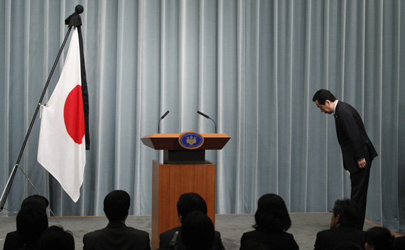 Japan's Prime Minister Naoto Kan bows to the national flag as he arrives for a news conference at his official residence in Tokyo April 1, 2011.