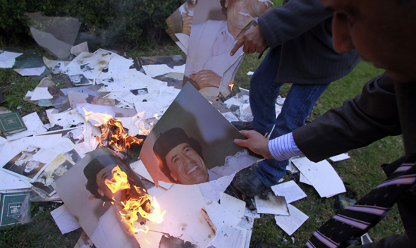 Employees of the Libyan Embassy burn portraits of Libyan leader Muammar Gaddafi at the embassy's garden in Buenos Aires August 23, 2011.
