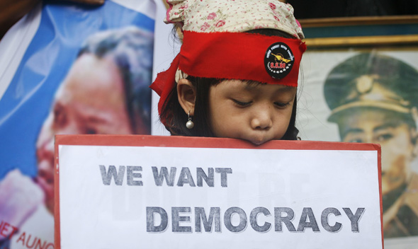 A girl of Myanmar heritage holds a placard during a pro-democracy rally in New Delhi August 8, 2011.