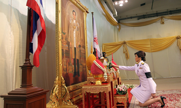 Thailand's first female PM Yingluck Shinawatra receives the royal command appointing her as the country's new premier in front of a portrait of Thai King Bhumibol Adulyadej in Bangkok.