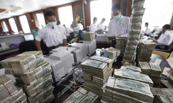 Cashiers are seen behind piles of kyat banknotes as they count it in a private bank in Yangon July 21, 2011.